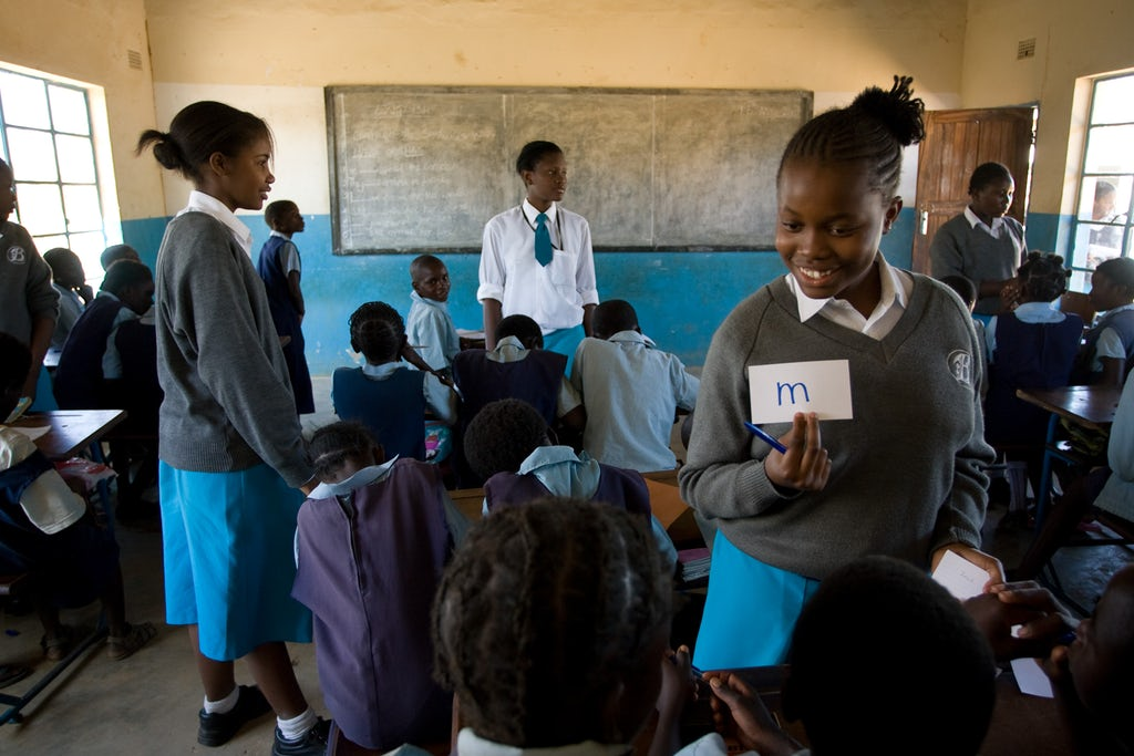 Students from Banani School (standing), a Bahá'í-inspired school in Chisamba, Zambia teach students at a nearby elementry school as part of a service project. Copyright © Bahá'í International Community